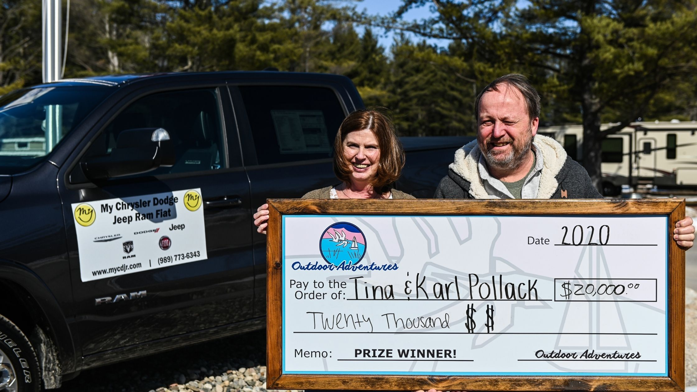Giveaway winners posed in front of the brand new truck, holding the $20,000 check they chose